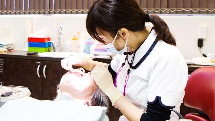 インプラント手術を行った患者のメンテナンスをしてる女性歯科医師